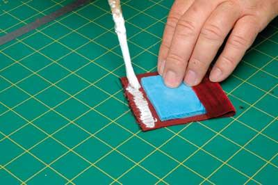 Glue velvet over pads of stiff foam using a flexible aliphatic resin