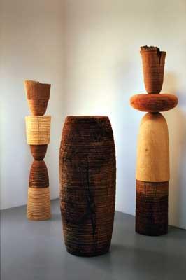 Mark Lindquist, Totemic Series Sculptures - (Left) Unmet Friend No.1, 1984, 1830mm (6ft) high x 430mm (15in) dia. walnut (Juglans regia), ash (Fraxinus excelsior) and maple (Acer campestre); (centre) Ancient Monolith No.1/Drum, 1984, walnut (Juglans regia); (Right) Silent Witness No.1 Oppenheiner, 1983, 2160mm (85in) high x 560mm (22in) dia. walnut (Juglans regia) pecan (Carya illinoiensis), elm (Ulmus americana)
